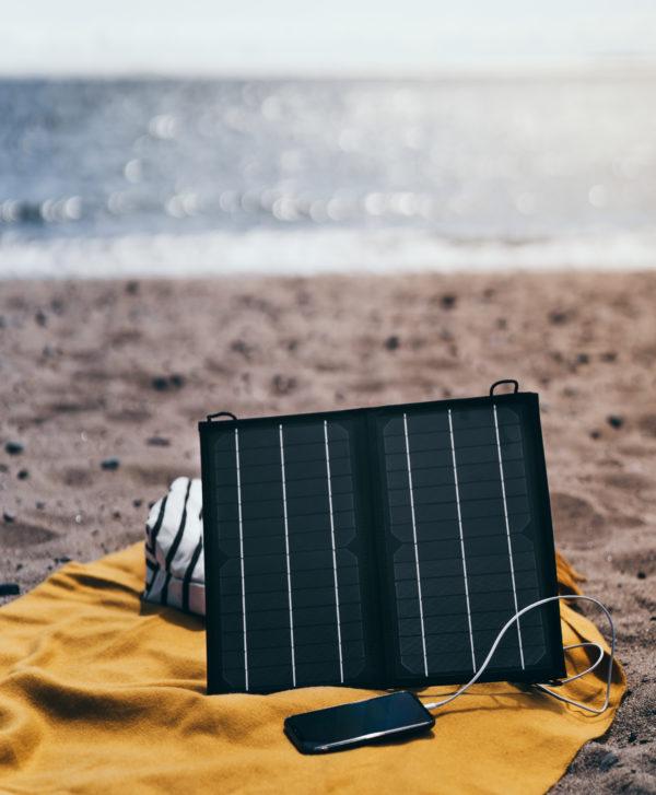 Kodak SP16 kannettava aurinkopaneeli uimarannalla kännykän akkua lataamassa